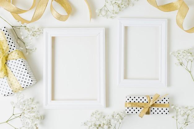 Cinta de oro; cajas de regalo; flores de aliento de bebé cerca del marco de madera sobre fondo blanco