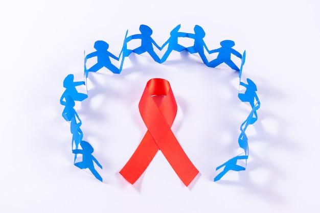 Cinta roja con cadena de personas hechas de papel cortado. día mundial del sida.