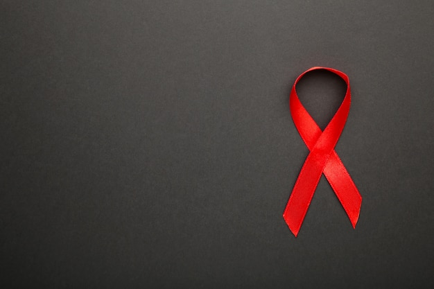 Cinta roja de concienciación sobre el sida en superficie negra