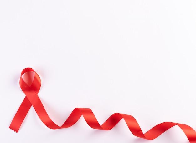 Cinta roja sobre fondo blanco. concepto del día mundial del cáncer. concepto del día mundial del sida.
