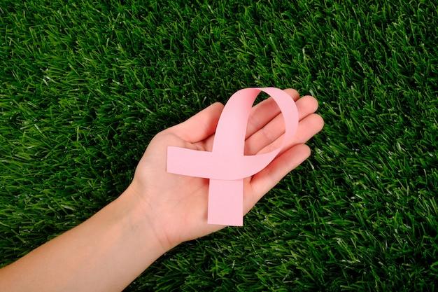 Cinta rosa en la mano en la palma sobre la hierba verde. símbolo de lucha contra el cáncer.