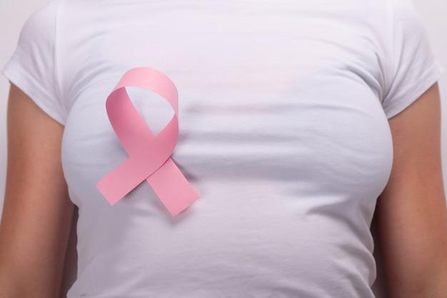 Cinta rosa en el pecho femenino, símbolo de lucha contra el cáncer de mama.