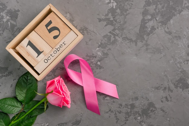 Cinta rosa, rosa y calendario de cubo de madera establecido para el 15 de octubre en superficie de concreto.