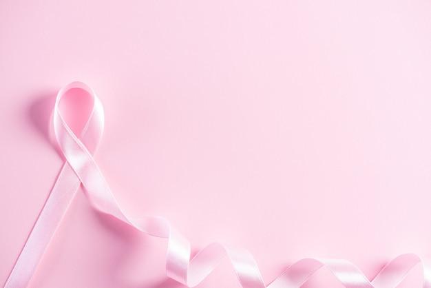 Cinta rosa sobre fondo de papel rosa para apoyar la conciencia del cáncer de mama