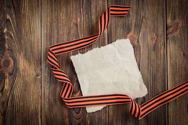 Cinta de san jorge y tarjeta de felicitación de papel sobre fondo de madera. día de la victoria o día del defensor de la patria.