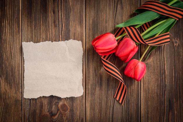 Cinta de san jorge, tulipanes rojos y tarjeta de felicitación de papel sobre fondo de madera. día de la victoria o día del defensor de la patria.