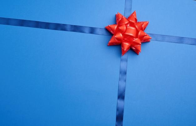 Cinta de seda azul cruzada sobre una superficie azul oscura en medio de un lazo rojo