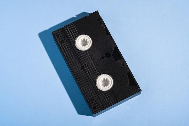 Cinta de video de plástico en formato vhs, cinta de almacenamiento magnética con tecnología retro analógica en una mínima pared azul pastel