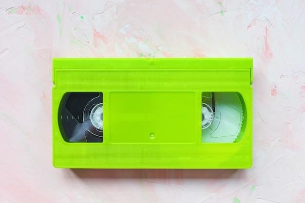Cinta de video vhs vintage verde sobre superficie rosa