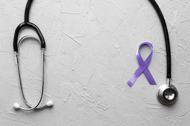 Cinta violeta cerca de estetoscopio negro sobre yeso