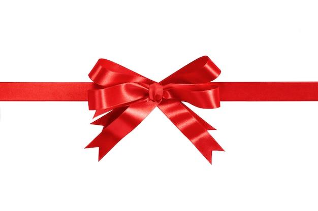Cinta y arco rojos del regalo aislados en blanco.