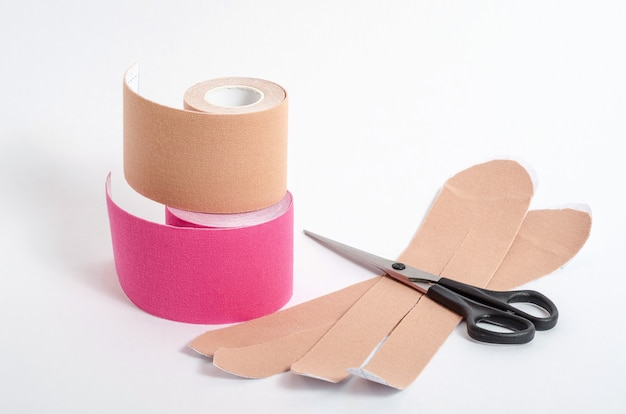 Cintas beige y rosa para la fijación de los músculos durante la práctica de deporte y después de lesiones sobre una superficie blanca con tijeras. vendaje kinesiológico de deportistas. rehabilitación y recuperación.