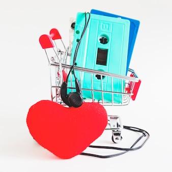 Cintas de casete en carro de compras con auricular y corazón rojo sobre fondo blanco