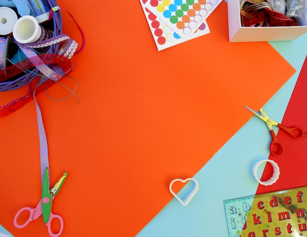 Cintas de colores, caja con hilos, moldes, tijeras y regla con letras en bac de colores