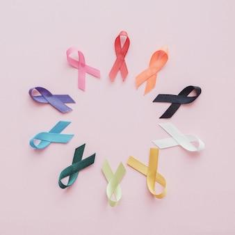 Cintas de colores sobre fondo rosa, conciencia del cáncer, día mundial del cáncer