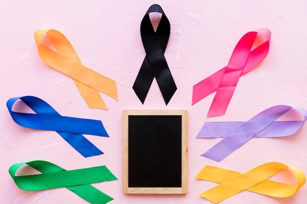 Cintas coloridas de la conciencia alrededor de la pequeña pizarra de madera en el contexto rosado