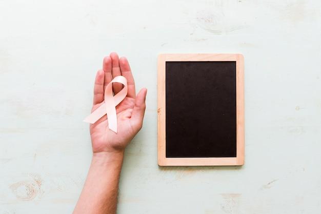 Cintas rosadas de la conciencia en la mano de la persona cerca de la pizarra en fondo rosado