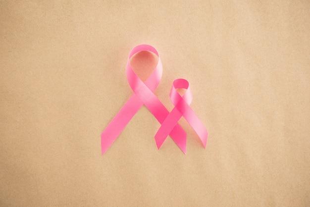 Cintas de satén rosa sobre papel marrón claro, símbolo de concienciación sobre el cáncer de mama.