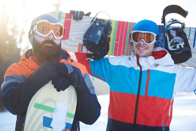 Cintura para arriba de dos snowboarders masculinos
