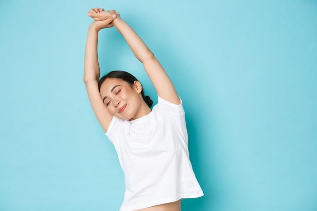 Cintura para arriba de la hermosa chica asiática que se siente relajada y feliz, cierra los ojos y estira las manos hacia los lados, sintiéndose llena de energía y optimista, lista para el nuevo día, de pie con fondo azul.