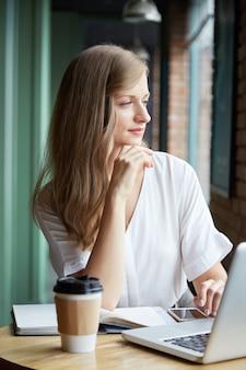 Cintura para arriba de pensativa joven sentada en el escritorio mirando por la ventana