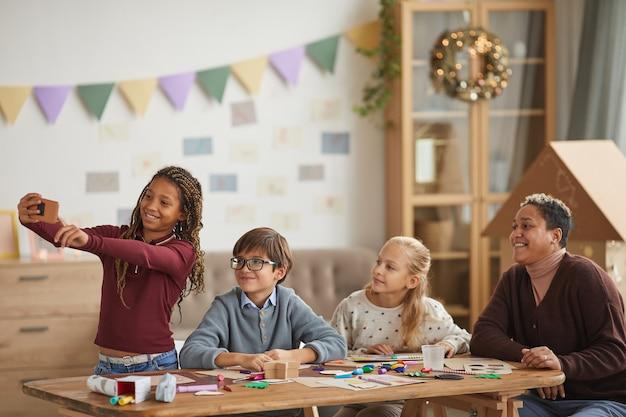 Cintura para arriba retrato de una adolescente afroamericana tomando selfie con niños y maestros durante la clase de arte y artesanía, espacio de copia