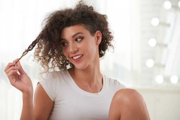 Cintura para arriba retrato de dama rizada jugando con su cabello