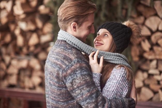 Cintura para arriba retrato de despreocupado joven y mujer abrazando y sonriendo. están de pie en el bosque de invierno y mirando a la cámara con felicidad.