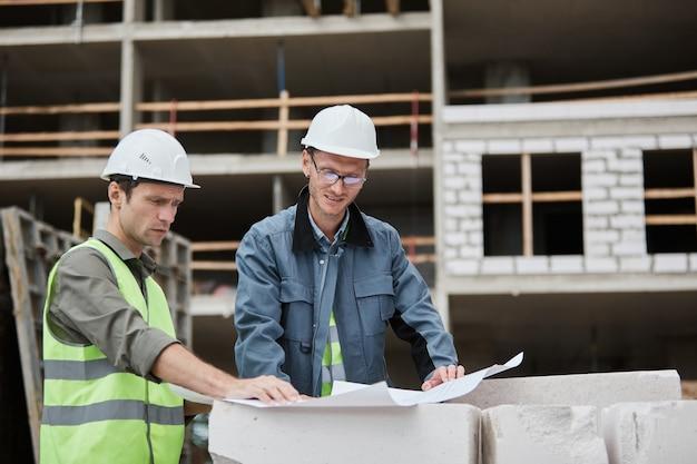 Cintura para arriba retrato de dos trabajadores discutiendo planos de planta en el espacio de copia del sitio de construcción