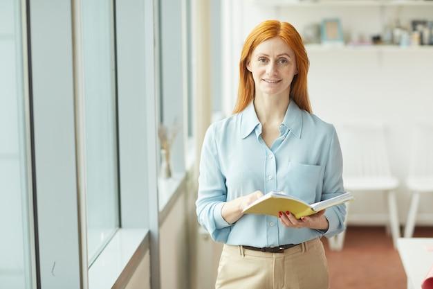 Cintura para arriba retrato de empresaria pelirroja sonriendo y sosteniendo el planificador mientras está de pie junto a la ventana en la moderna oficina blanca, espacio de copia