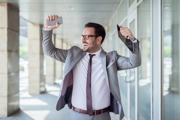 Cintura para arriba retrato del empresario celebrando el éxito. en una tableta de mano y en otro teléfono inteligente. centro de negocios exterior.