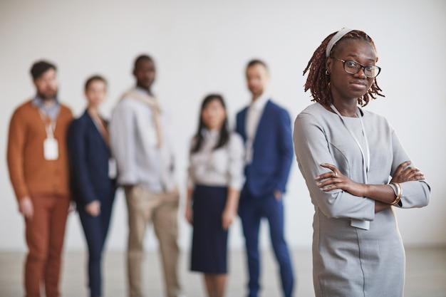 Cintura para arriba retrato de exitosa empresaria afroamericana de pie con los brazos cruzados contra el equipo multiétnico en segundo plano, espacio de copia