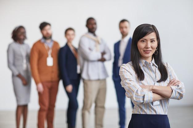 Cintura para arriba retrato de exitosa empresaria asiática sonriendo a la cámara mientras está de pie con equipo multiétnico en segundo plano, espacio de copia