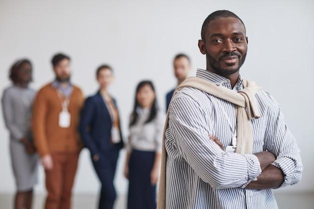Cintura para arriba retrato de exitoso empresario afroamericano sonriendo a la cámara mientras está de pie con equipo multiétnico en segundo plano, espacio de copia