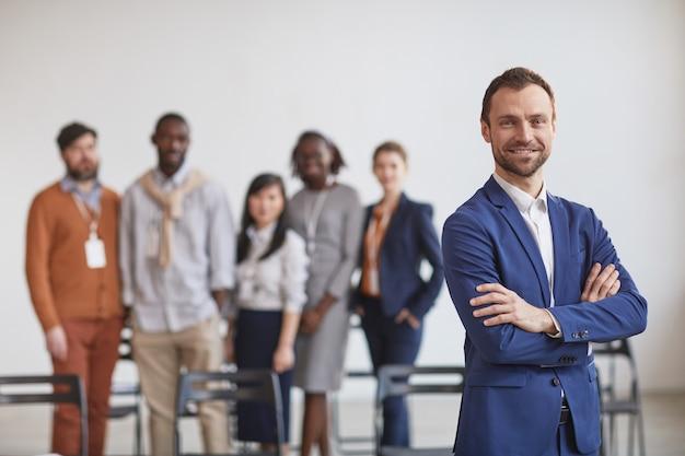 Cintura para arriba retrato del exitoso empresario de pie con los brazos cruzados contra el equipo multiétnico en segundo plano, espacio de copia