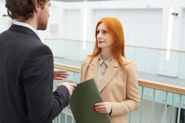 Cintura para arriba retrato de gerente mujer pelirroja hablando con su colega mientras está de pie en el balcón en el interior de la oficina blanca, espacio de copia