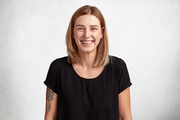 Cintura para arriba retrato de hermosa mujer joven sonriente con expresión positiva, viste camiseta negra casual, tiene el brazo tatuado, modelos contra la pared de hormigón