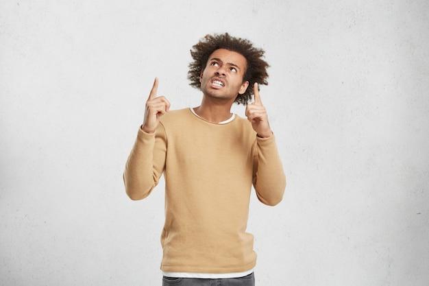 Cintura para arriba retrato de hombre descontento con peinado tupido, presiona los dientes e indica al revés