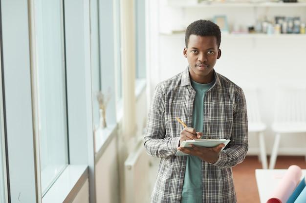 Cintura para arriba retrato de joven afroamericano sosteniendo el portapapeles durante la pasantía empresarial, espacio de copia