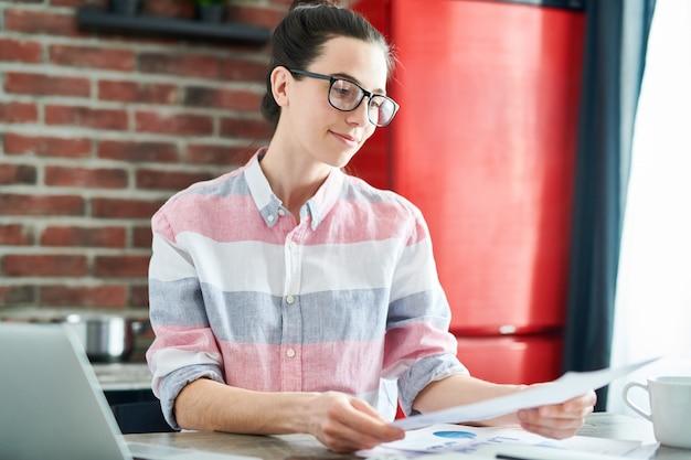 Cintura para arriba retrato de joven sonriente leyendo documentos mientras trabaja o estudia en casa