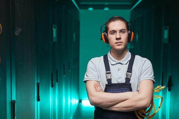 Cintura para arriba retrato de joven técnico de red mirando a la cámara mientras está de pie con los brazos cruzados en la sala de servidores, espacio de copia