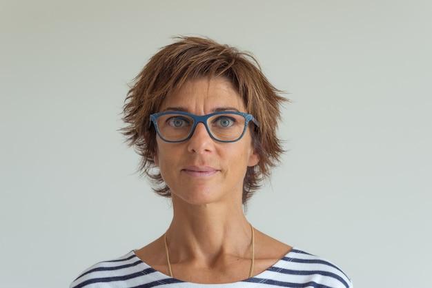Cintura para arriba retrato de mujer adulta con pelos rojos, ojos azules verdes