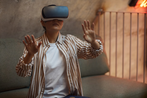 Cintura para arriba retrato de mujer asiática con equipo vr y gesticulando mientras disfruta de una experiencia inmersiva en un interior futurista