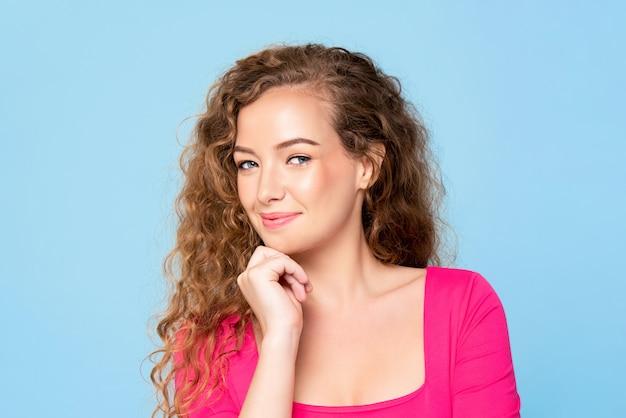 Cintura para arriba retrato de mujer caucásica bastante feliz en blusa rosa sonriendo con la mano en el mentón aislado