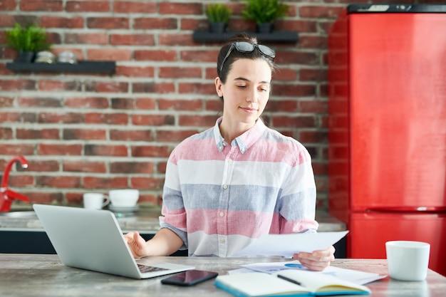 Cintura para arriba retrato de mujer joven moderna usando laptop y leyendo documentos mientras trabaja o estudia en casa