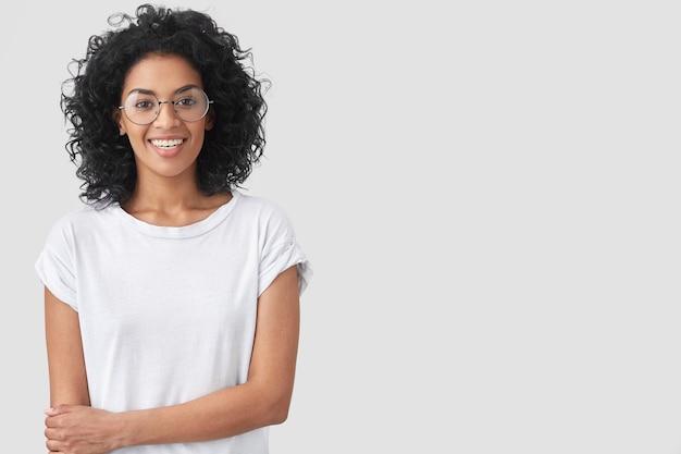 Cintura para arriba retrato de mujer de piel oscura feliz con peinado afro, sonríe suavemente