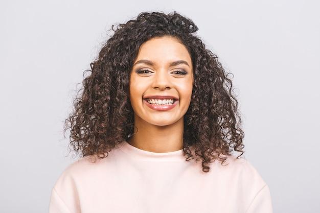 Cintura para arriba retrato de mujer de raza mixta joven alegre con pelo rizado posando en estudio con sonrisa feliz. mujer de piel oscura vestida casualmente sonriendo con alegría, mostrando sus dientes rectos blancos