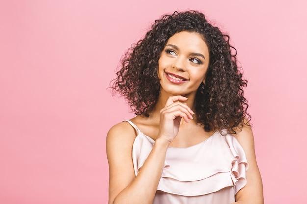 Cintura para arriba retrato de mujer de raza mixta joven alegre con pelo rizado posando en estudio con sonrisa feliz. mujer de piel oscura en vestido sonriendo con alegría, mostrando sus dientes rectos blancos