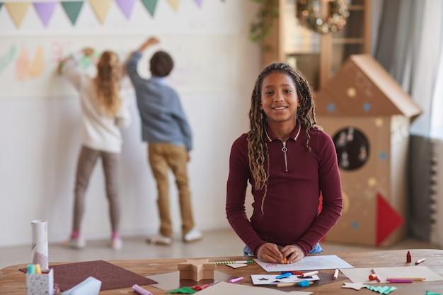 Cintura para arriba retrato de niña afroamericana sonriente mirando a la cámara mientras está de pie junto a la mesa de elaboración y disfruta de la clase de arte en la escuela, espacio de copia