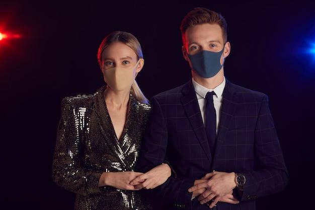 Cintura para arriba retrato de pareja joven con máscaras faciales y mirando a la cámara mientras posa en la fiesta de pie contra el fondo negro